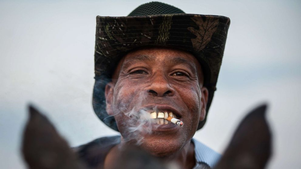A cowboy named James shows off his golden grill while smoking a cigarette in Bolivar County, Miss.