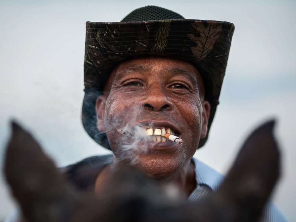 PHOTO: A cowboy named James shows off his golden grill while smoking a cigarette in Bolivar County, Miss.