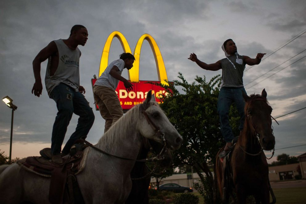 A group of young cowboys dance atop their horses in the McDonald's parking lot in Cleveland, Miss.