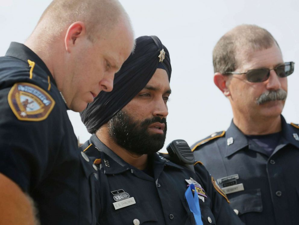 PHOTO: In this Aug. 30, 2015, photo, Harris County Sheriffs Deputy Sandeep Dhaliwal, center, grieves with Deputies Dixon, left, and Seibert, right, at a memorial for Deputy Darren Goforth, at the Chevron where he was killed, in Houston.