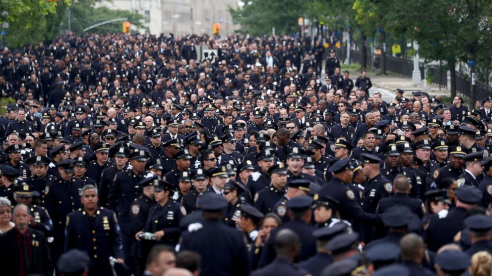 Police officers line up outside the funeral of slain New York Police Department (NYPD) Officer, Miosotis Familia, outside of the World Changers Church in the Bronx, New York, July 11, 2017. Officer Familia, who was a 48-year-old mother of three, was shot while sitting in her patrol car in the Bronx; her assailant was killed by police after the attack.