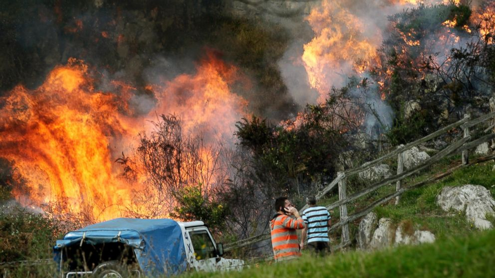 Two neighbors look at the flames as firefighters work to extinguish a forest fire at Ribera de Arriba in Asturias, Spain, Dec. 28, 2015.