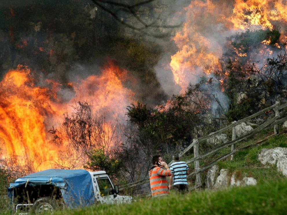 PHOTO:Two neighbors look at the flames as firefighters work to extinguish a forest fire at Ribera de Arriba in Asturias, Spain, Dec. 28, 2015.