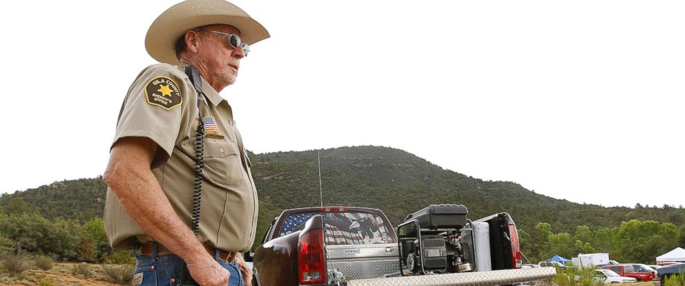 PHOTO: Gila County Sheriffs Office deputy Larry Hassinger stands watch at the entrance to the First Crossing recreation area during a search and rescue operation for victims of a flash flood, July 16, 2017, in Payson, Ariz.