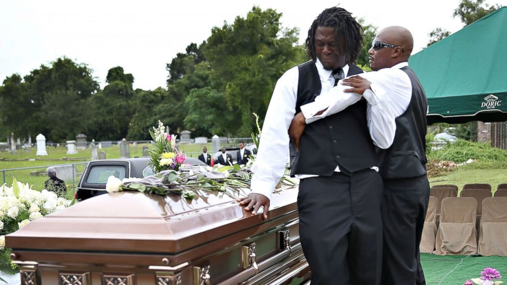 Brandon Risher, left, is comforted beside the casket of his grandmother, Ethel Lance, 70, one of nine victims of a mass shooting at the Emanuel AME Church, before she is buried at the church cemetery, June 25, 2015 in North Charleston, South Carolina.