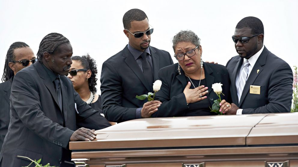 Sharon Risher, 2nd from right, and Gary Washington, left, pay their respects at the casket of their mother, Ethel Lance, 70, before her burial at the AME Church cemetery, June 25, 2015, in North Charleston, South Carolina. Lance was one of nine people shot to death inside Mother Emanuel AME Church.