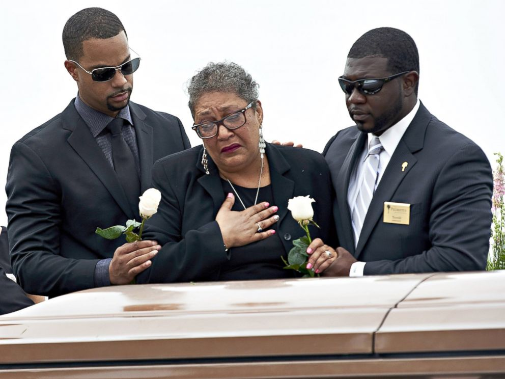 PHOTO: Sharon Risher, 2nd from right, and Gary Washington, left, pay their respects at the casket of their mother, Ethel Lance, 70, before her burial at the AME Church cemetery, June 25, 2015, in North Charleston, S.C.
