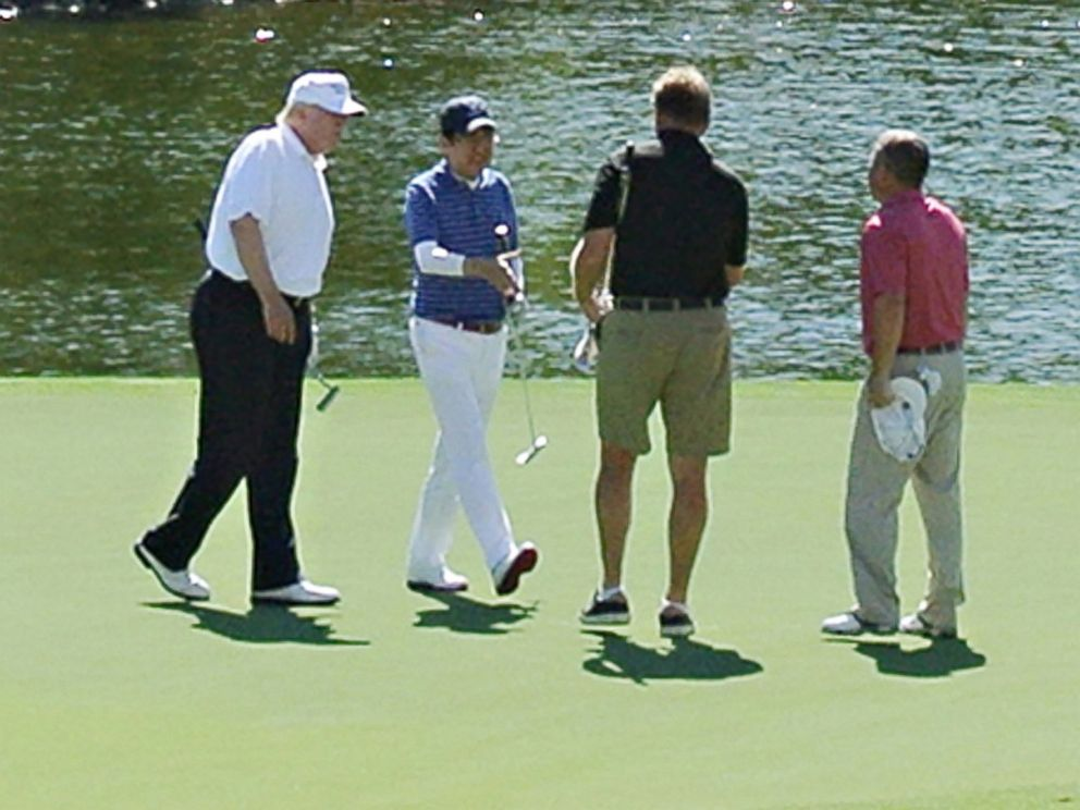 PHOTO: President Donald Trump, wearing black pants, and Japans Prime Minister Shinzo Abe, third from right, enjoy playing golf, Feb. 11, 2017, in Florida.