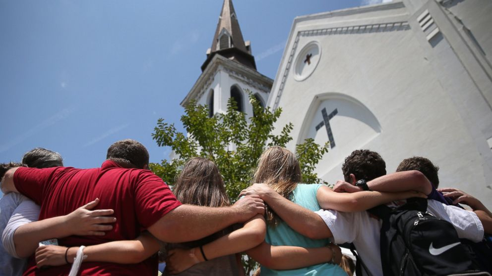 A church youth group from Dothan, Alabama prays in front of the Emanuel AME Church on the one-month anniversary of the mass shooting, July 17, 2015, in Charleston, South Carolina. Dylann Roof was convicted for the killing of nine church members.