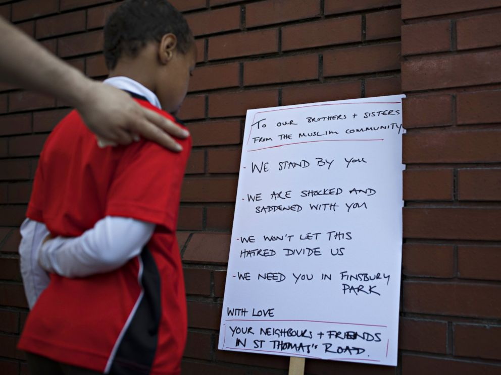PHOTO: A boy reads a sign outside Finsbury Park Mosque on June 19, 2017 in London. Worshippers were struck by a hired van as they were leaving the mosque following Ramadan prayers