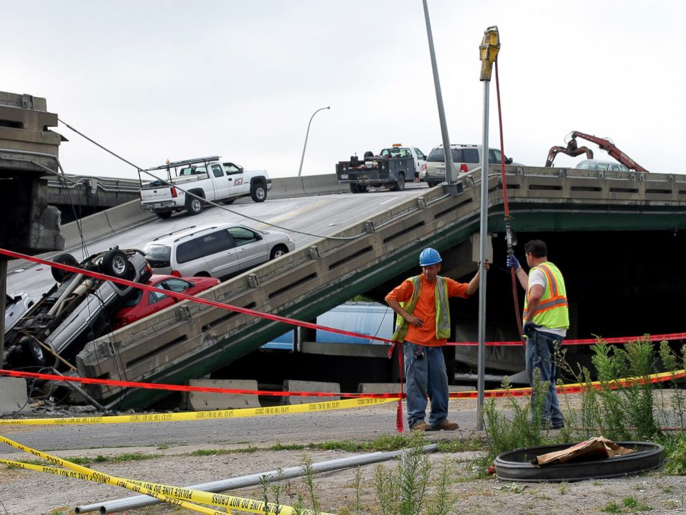 PHOTO: Workers build a metal fence, Aug. 7, 2007, along police tape where the I-35W bridge collapsed over the Mississippi River in Minneapolis, Minnesota.