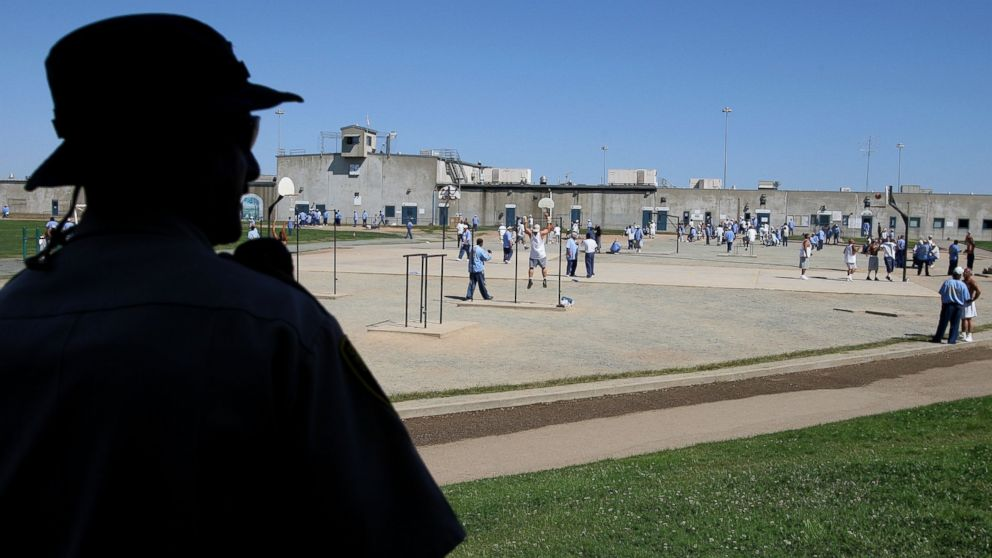 A California Department of Corrections officer looks on as inmates at the Mule Creek State Prison exercise in the yard August 28, 2007 in Ione, California.