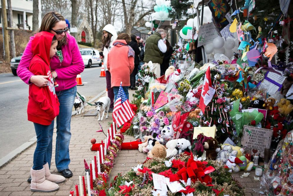 Deborah Gibelli holds her daughter, Alexandra Gibelli, age 9, while looking at a memorial for those killed in the school shooting at Sandy Hook Elementary School, on Dec. 24, 2012 in Newtown, Conn.
