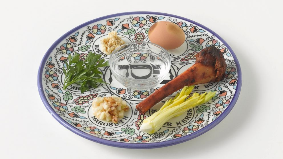 A Passover Seder of roasted egg, roasted bone, parsley, charoset, celery, nuts and salt water on a plate.