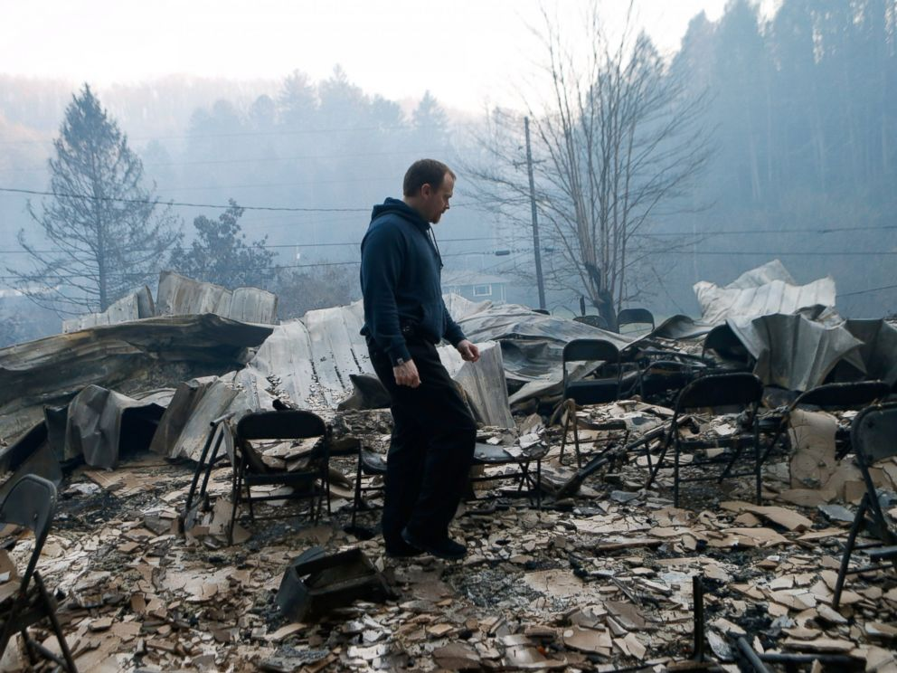 PHOTO: Trevor Cates, walks through the smoldering remains of the fellowship hall of his church, the Banner Missionary Baptist Church as he inspects damage after the wildfires, Nov. 29, 2016, in Gatlinburg, Tennessee.