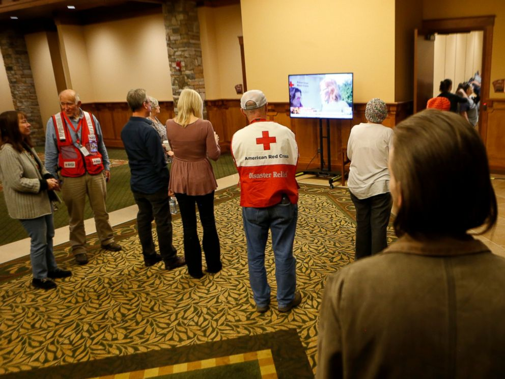 PHOTO: Volunteers and evacuees watch a news segment about the nearby fire in Gatlinburg, Tennessee at a shelter, on Nov. 29, 2016, in Pigeon Forge, Tennessee.