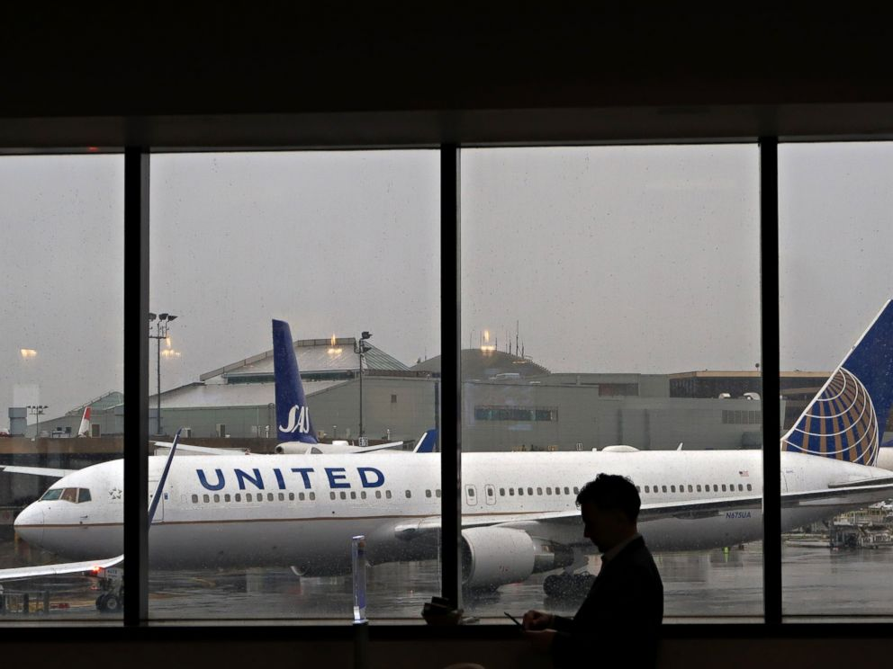 PHOTO: A man uses his mobile phone in front of a United Airlines plane at Newark Liberty Airport, April 6, 2017, in Newark, NJ.