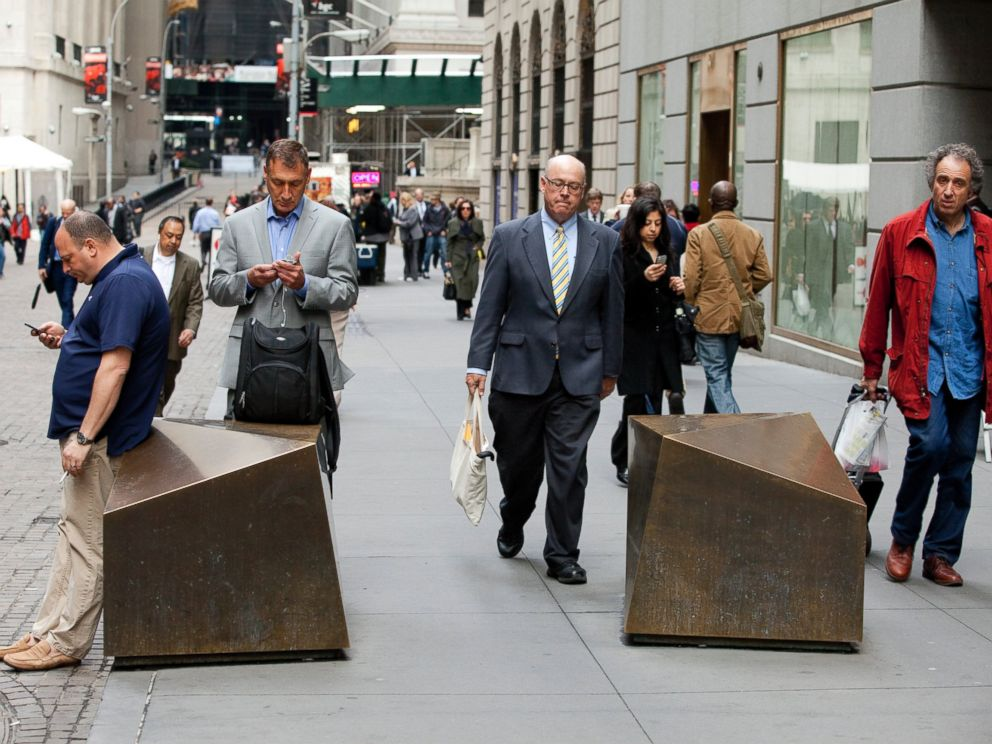 PHOTO: Commuters walk to work down Wall Street past artistic security barricades near the NYSE, April 11, 2013 in New York.