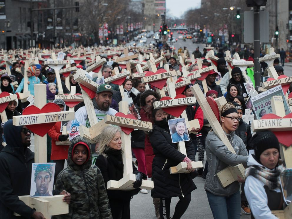 PHOTO: Residents, activists, and friends and family members of victims of gun violence march down Michigan Avenue carrying nearly 800 wooden crosses bearing the names of people murdered in the city in 2016, Dec. 31, 2016 in Chicago.