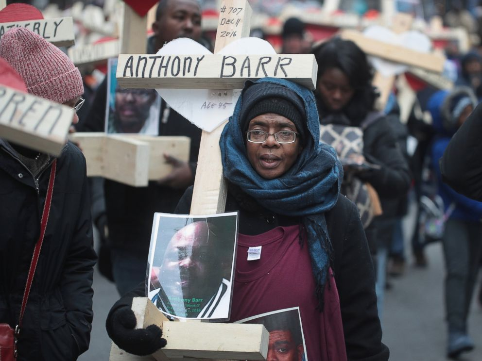 PHOTO: Melva Pratt carries a cross as she marches with other residents, activists, and family members of victims of gun violence down Michigan Avenue, Dec. 31, 2016 in Chicago.