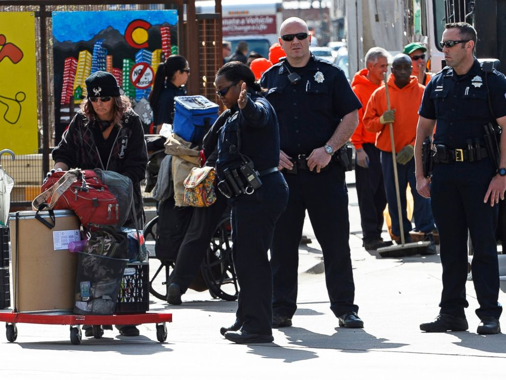 PHOTO: Homeless people remove their belongings as Denver Police and Sheriff deputies oversee their progress and enforce the law at the intersections of Broadway and Park Ave West in Denver, Colorado, March 8, 2016 in Denver, Colorado.