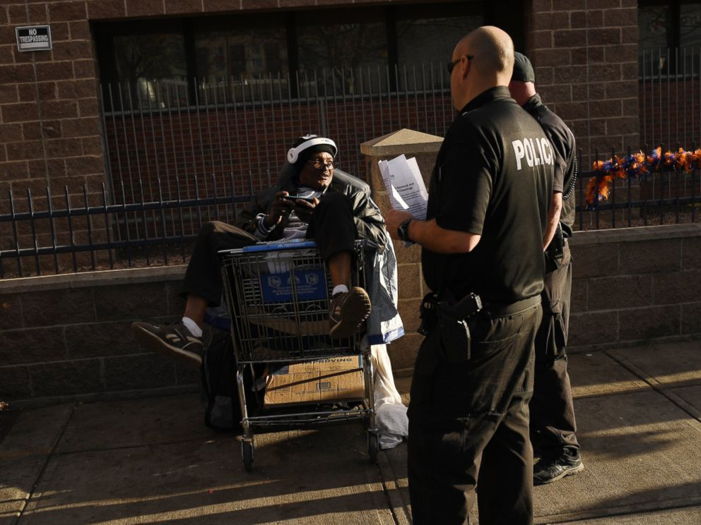 PHOTO: Denver police hand out information to homeless before crews began to sweep the homeless camps on Lawrence Street near Samaritan House, Nov. 14, 2016.
