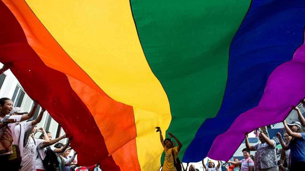 Participants parade the rainbow color flag during a gay pride march in Manila, June 24, 2017.