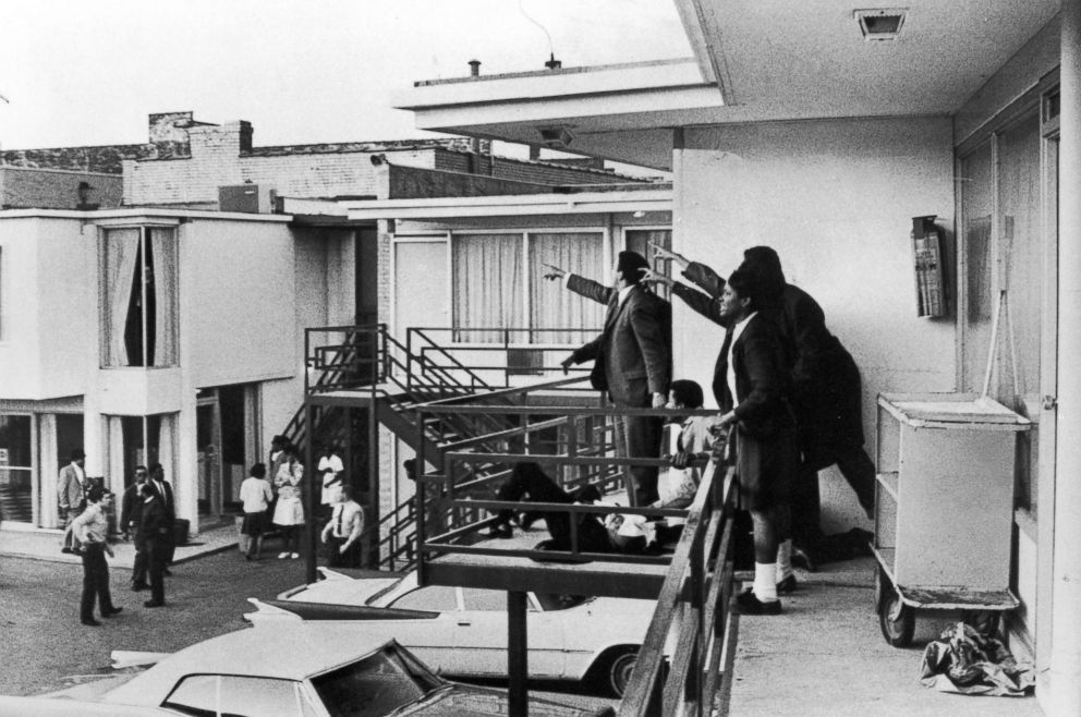 PHOTO: Civil rights leader Andrew Young, left, and others stand on the balcony of the Lorraine motel pointing in the direction of the shooter after the assassination of civil rights leader Dr. Martin Luther King, Jr., who is lying at their feet.