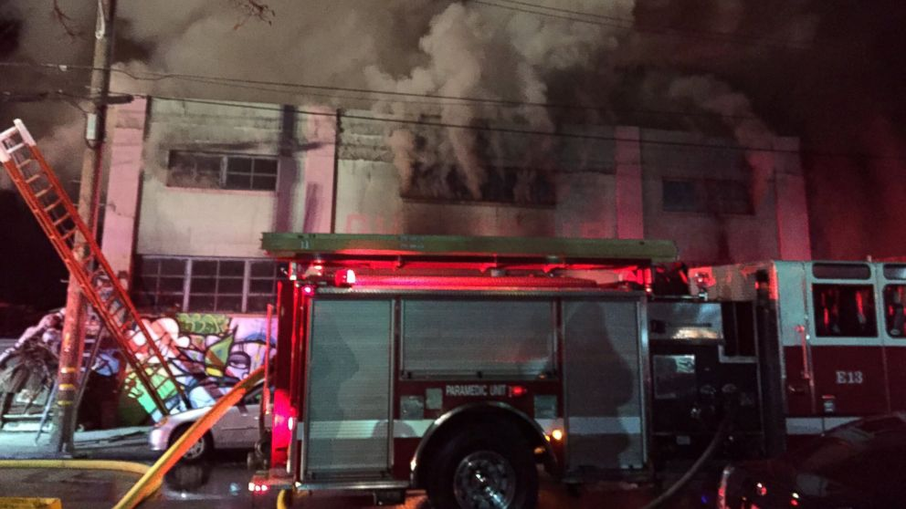 Smoke pours from a warehouse, which caught fire during a dance party in Oakland, California, Dec. 3, 2016.