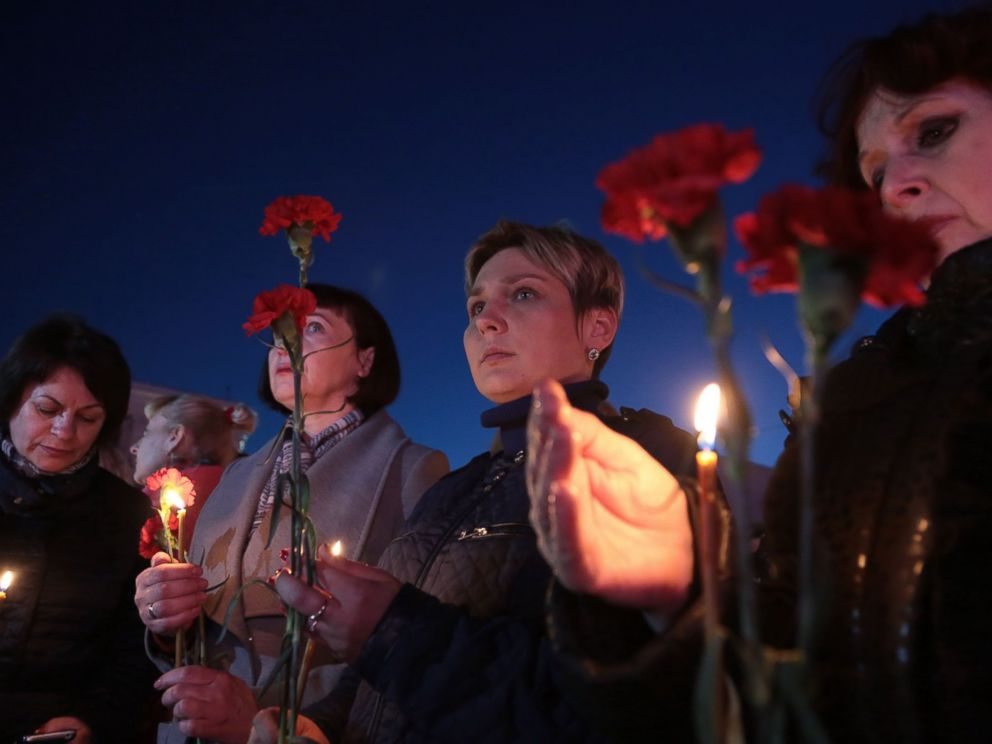 PHOTO: Women hold flowers and candles as they take part in a vigil in honor of the victims of the blast in the Saint Petersburg metro in Simferopol, Crimea, on April 3, 2017.