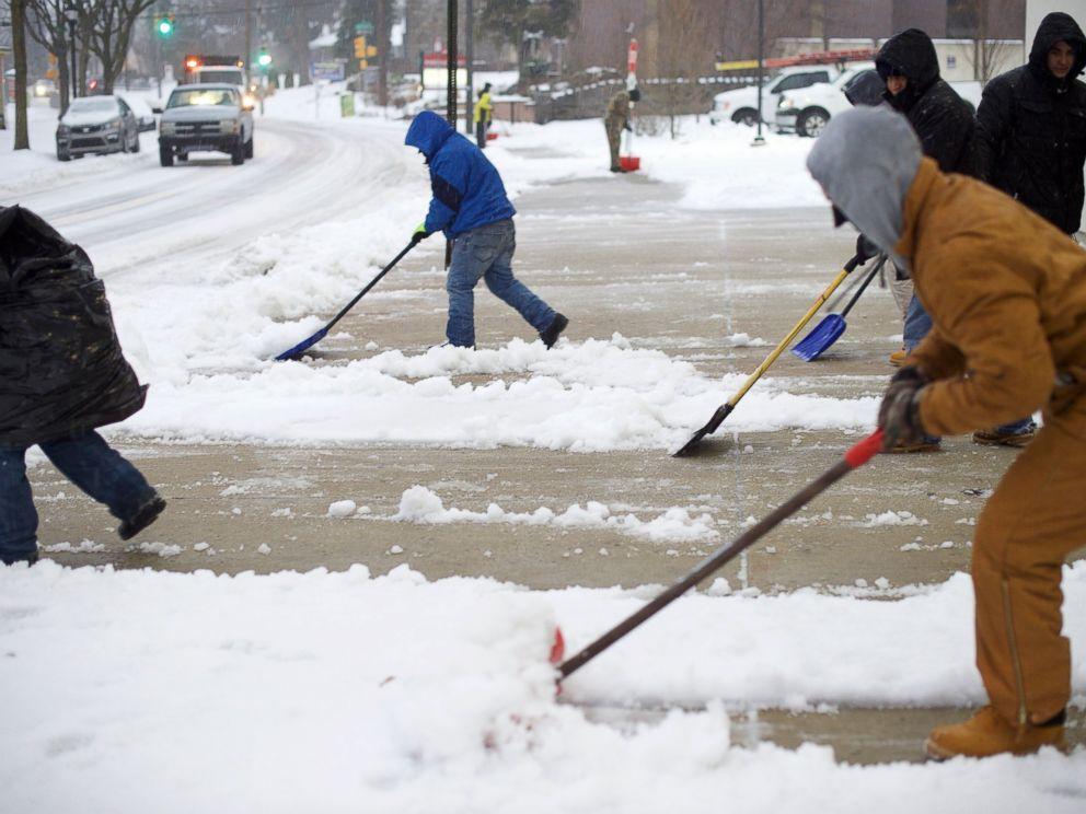 PHOTO: Men shovel a sidewalk March 14, 2017 in the Roxborough area of Philadelphia.
