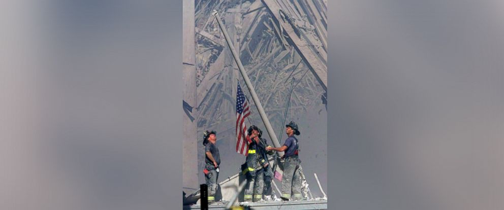 PHOTO: Firefighters raise a U.S. flag at the site of the World Trade Center after two hijacked commercial airliners were flown into the buildings on Sept. 11, 2001 in New York City.