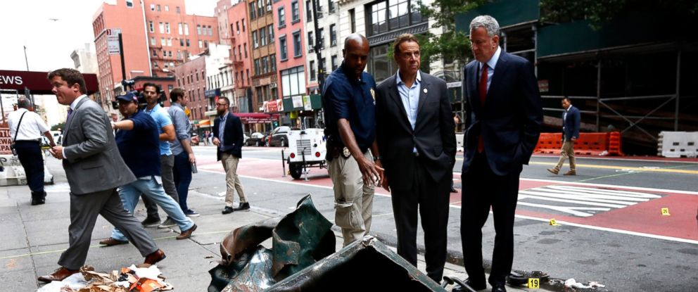 PHOTO: New York Mayor Bill de Blasio (R) and New York Governor Andrew Cuomo (C) stand in front of a mangled dumpster while touring the site of an explosion that occurred, on Sept. 18, 2016, in the Chelsea neighborhood of New York City.