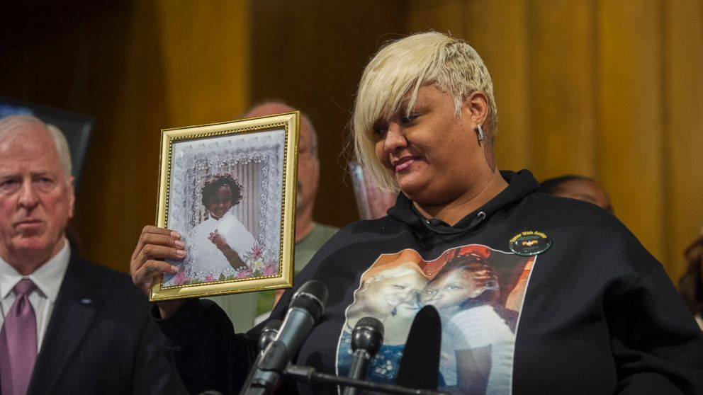 WASHINGTON, DC - DECEMBER 11: Ashake Banks, of Chicago Illinois, introduces herself to the audience as she holds a photo of her daughter Heaven Sutton, 7, who was shot by a stray bullet while operating her sidewalk lemonade stand on Chicago's west side on June 27, 2012.