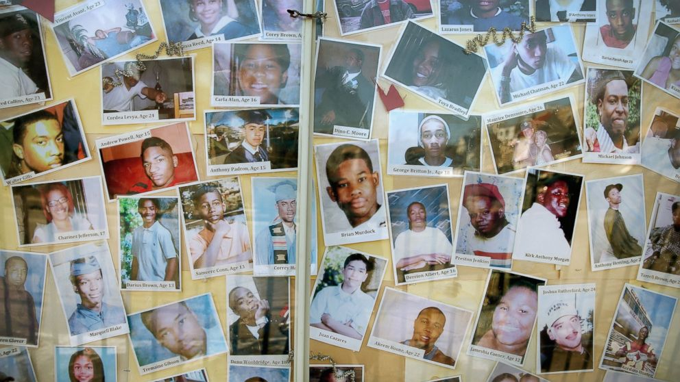 CHICAGO, IL - DECEMBER 23: Pictures of Chicago residents who have died by gunfire are posted next to a Christmas tree outside Saint Sabina Church in the Auburn Gresham neighborhood on the city's Southside on December 23, 2013 in Chicago, Illinois. Nearly 1,000 people have been murdered in Chicago in the past two years, more than any other U.S. city. (Photo by Scott Olson/Getty Images)
