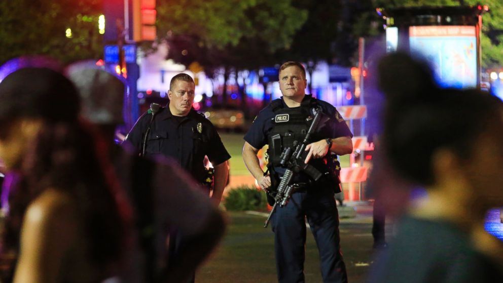 Dallas police and residents stand near the scene where Dallas police officers were shot and killed on July 7, 2016 in Dallas, Texas.