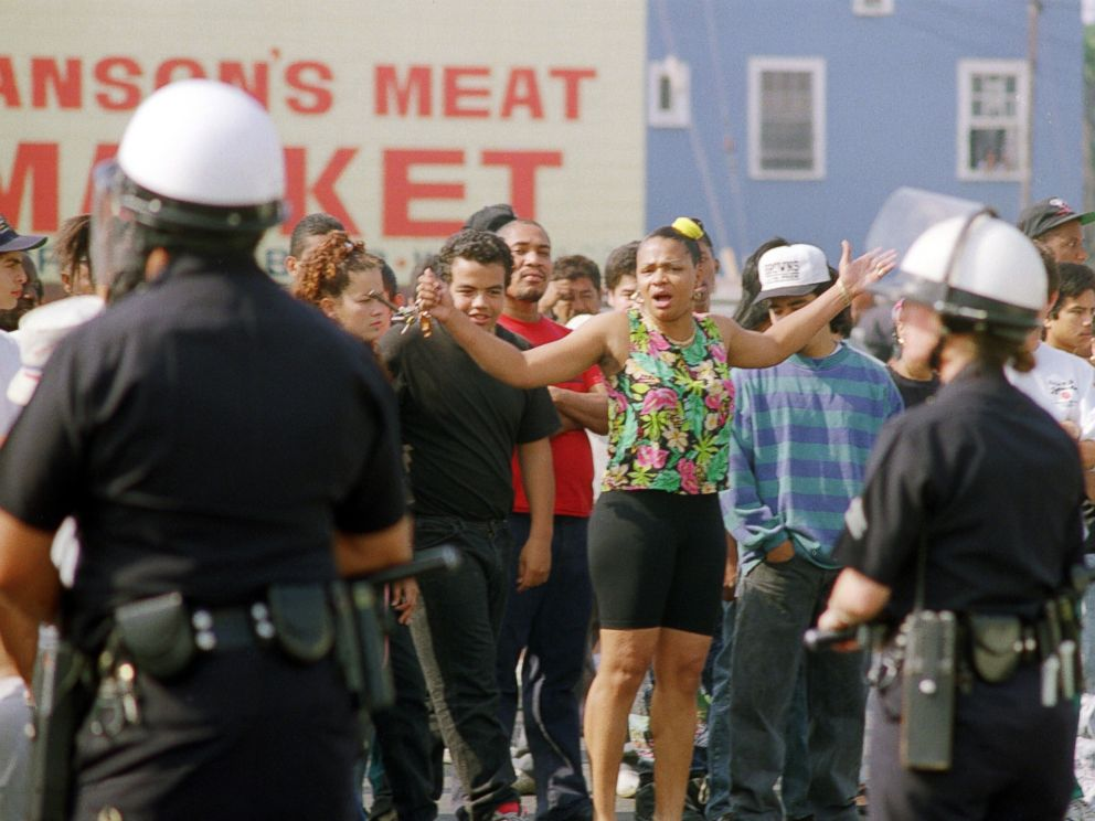 PHOTO: A woman yells at Los Angeles police officers who stand guard outside a shopping center, April 30, 1992, in Los Angeles.