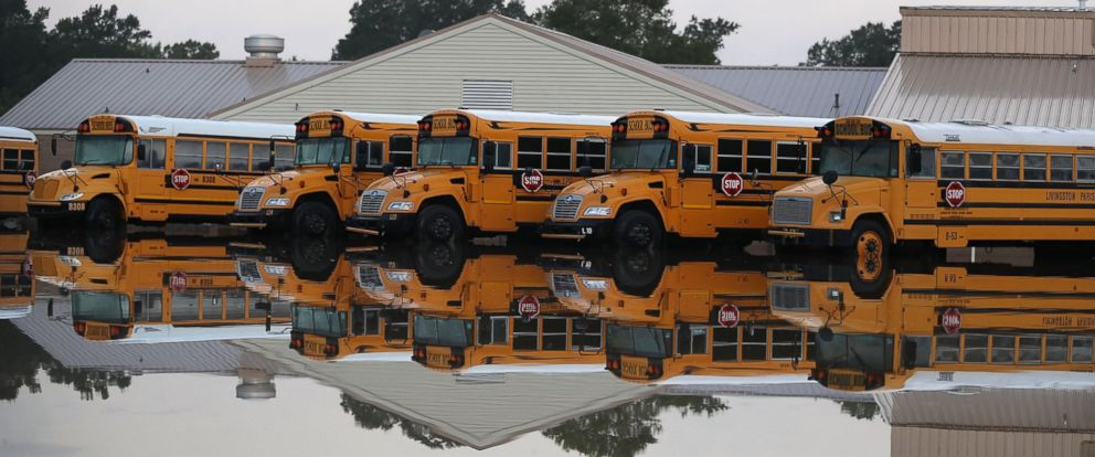 PHOTO: School buses are parked in a flooded parking lot, on Aug. 16, 2016, in Denham Springs, Louisiana.