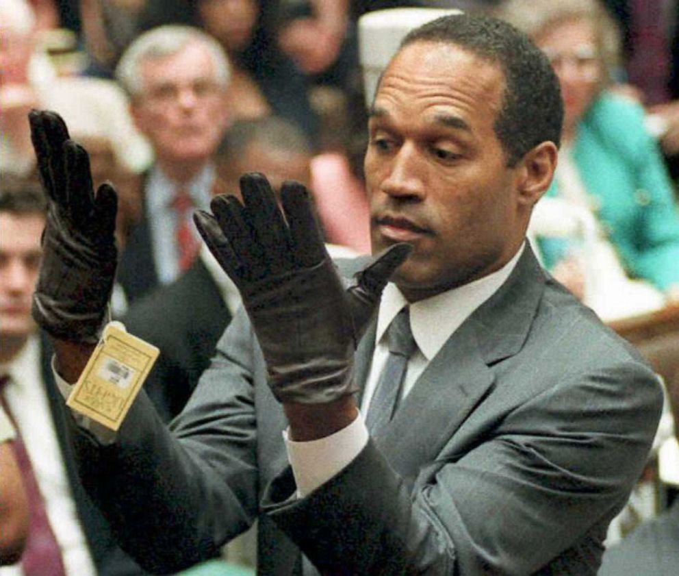 PHOTO: O.J. Simpson looks at a new pair of Aris extra-large gloves that prosecutors had him put on June 21,1995 during his double-murder trial in Los Angeles.