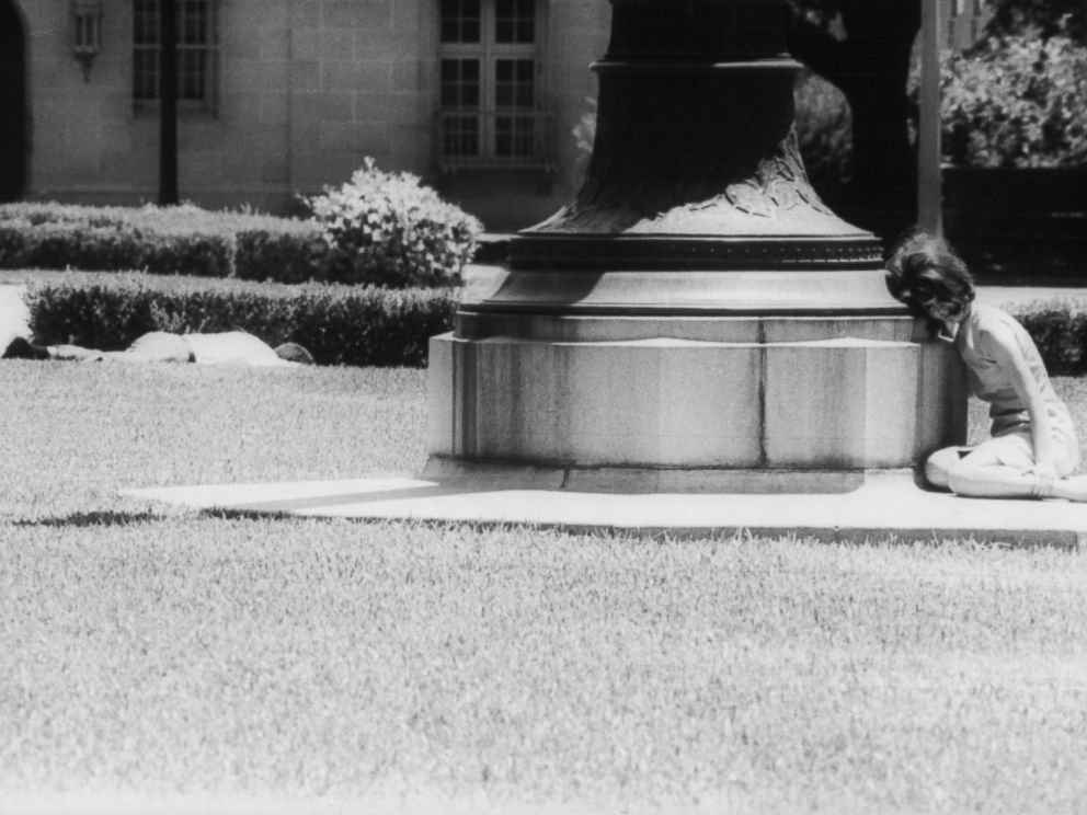 PHOTO: A woman cowers in fear behind a statue while a man lies wounded a few feet away, victim of sniper Charles Whitman, Aug. 1, 1966, in Austin, Texas.