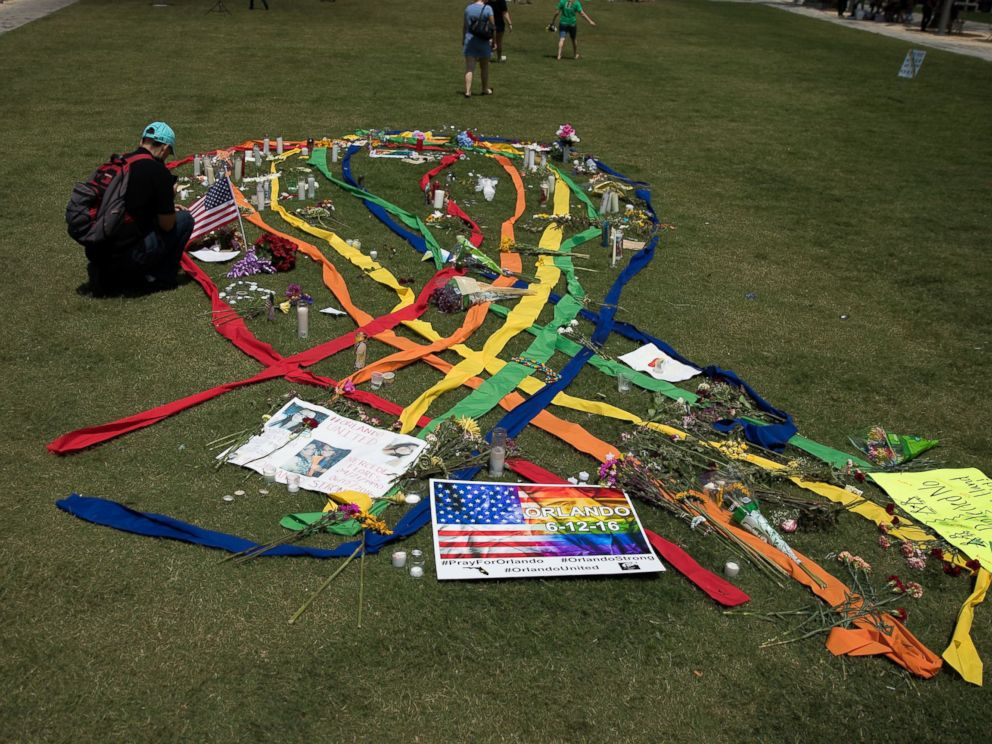 PHOTO: A gay pride ribbon is displayed on the lawn of the Dr. Phillips Performing Arts Center, near a makeshift memorial for the victims of the Pulse Nightclub shooting June 14, 2016 in Orlando, Florida.