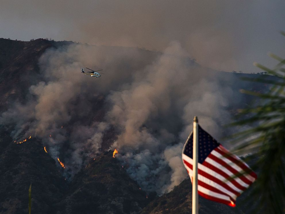 PHOTO: A Los Angeles County Fire helicopter flies over smoke and flames at the San Gabriel Complex Fire in the Angeles National Forest, June 21, 2016 near Duarte, Calif.