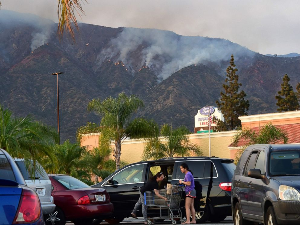PHOTO: Shoppers load their car with the purchases against the backdrop of the smoke from the San Gabriel Complex Fire in the Angeles National Forest, near Duarte, Calif., on June 21, 2016.