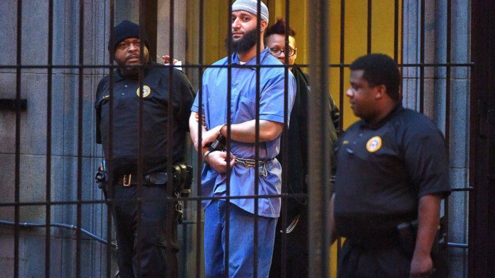 """Officials escort """"Serial"""" podcast subject Adnan Syed from the courthouse following the completion of the first day of hearings for a retrial in Baltimore,  Feb. 3, 2016."""