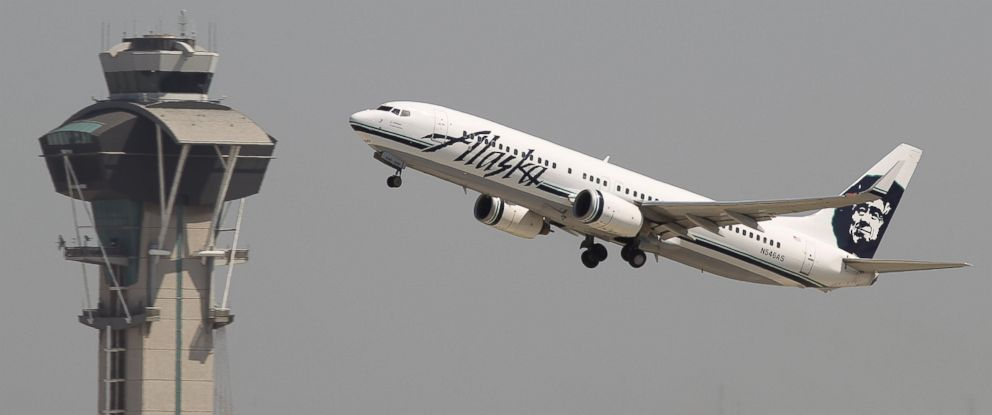 PHOTO: An Alaska Airlines jet passes the air traffic control tower at Los Angles International Airport (LAX) during take-off.