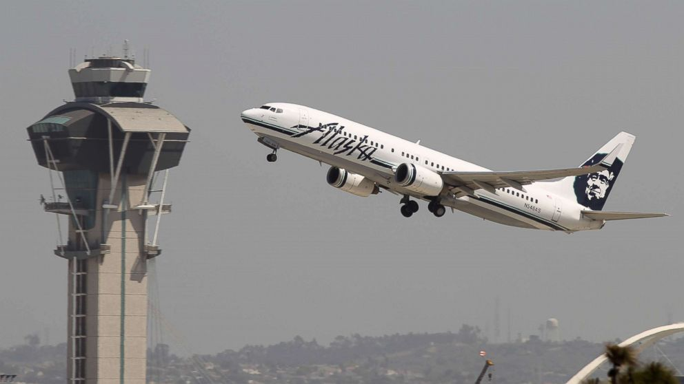 An Alaska Airlines jet passes the air traffic control tower at Los Angles International Airport (LAX) during take-off.