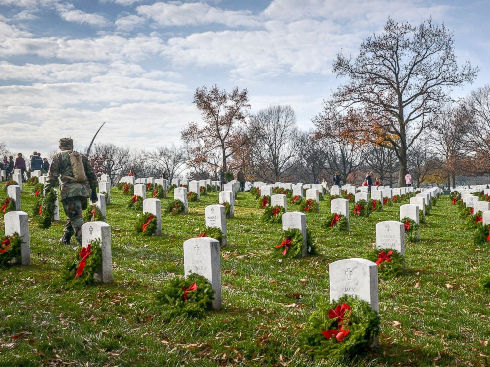 PHOTO: Volunteers carry wreaths in search of unadorned gravesite during as they participate in Wreath Across America, to lay wreaths on each grave in Arlington National Cemetery, Dec. 12, 2015, in Arlington.