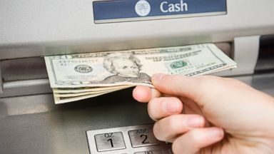 PHOTO: A person withdraws cash from ATM machine.