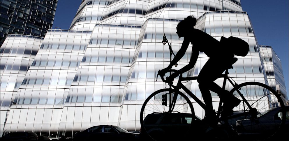 PHOTO: Silhouette of a cyclist who passes the InterActiveCorp building in New York, May 14, 2013.