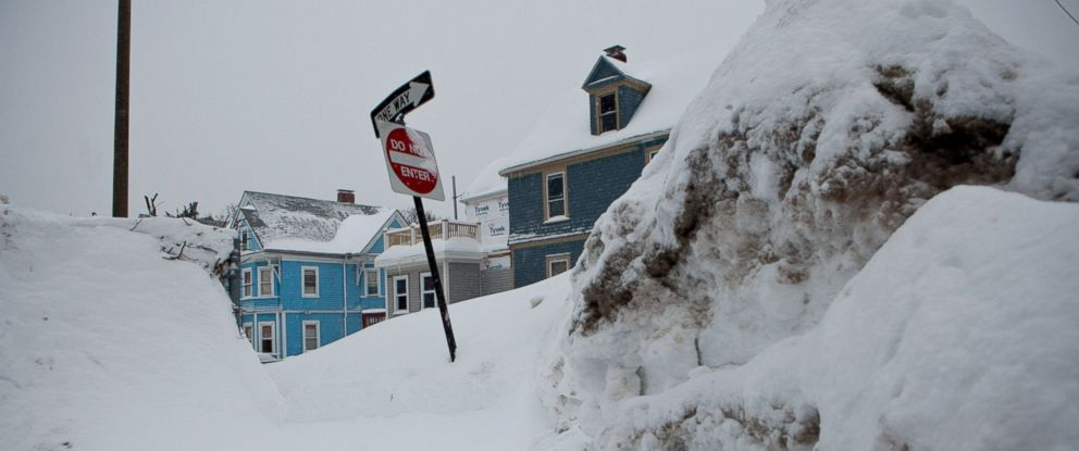 PHOTO: Snow banks from prior snowstorms rise above street signs on the corner of a residential street on Feb.9, 2015, in the Dorchester neighborhood of Boston, Mass.